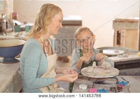 Smiling female potter and girl working in potter workshop
