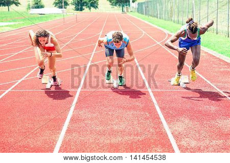 Runners at start grid front view on red athletics track - Professional sprinters explosive speed training - Concept of preparation for sports events and international competition -