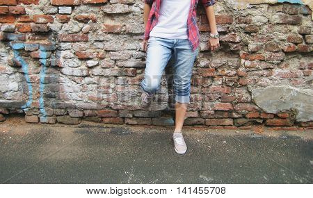 Lifestyle portrait of stylish young person in casual clothes: white t-shirt, plaid shirt, blue jeans and gray shoes standing against urban brick wall background.