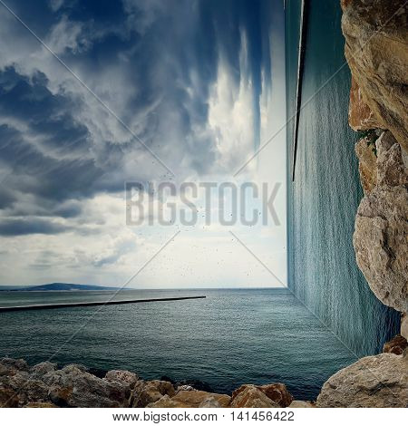 Surreal background of two worlds collide at the coast of the sea. Sea landscape between two piers on the stone beach with a dramatic cloudy sky.