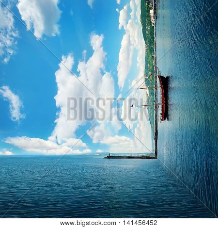 Surreal background of two worlds collide at the coast of the sea. Clear morning view with a sail boat floating. Summer vacation joy and recreation concept.