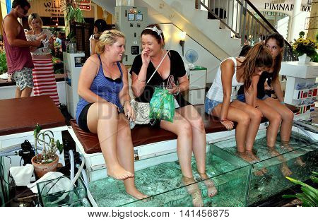 Patong City / Phuket Thailand - January 2 2012: Four western tourists getting a fish massage at the Jung Ceylon shopping center