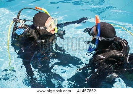 Couple practicing scuba diving together in the swimming pool