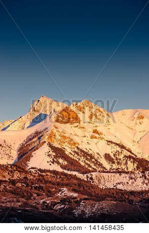 Winter sunset on the Arche and Aiguille peaks covered in snow in Ecrins National Park of the Southern French Alps (Hautes Alpes). France