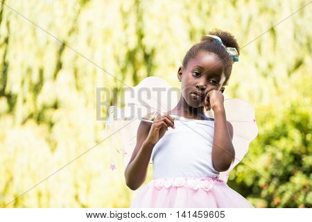 Cute mixed-race girl posing and wearing a fairy dress on a park