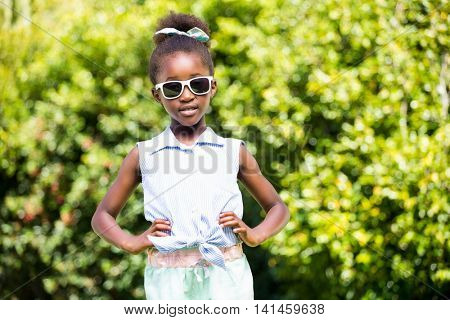 Cute mixed-race girl posing with sunglasses on a park