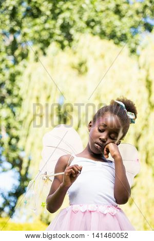 Cute mixed-race girl boring and wearing a fairy dress on a park