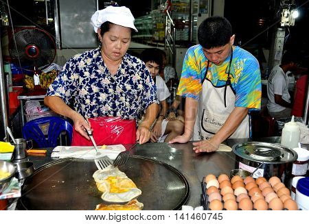 Hua Hin Thailand - December 29 2009: Woman with her son cooking a Tbai egg crêpe in her stall at the Dechanuchit Road Night Market