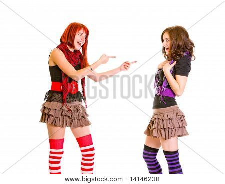 Pleased young girl pointing fingers at her amazed girlfriend isolated on white