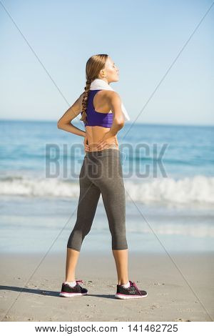 Beautiful woman taking break after exercising on the beach