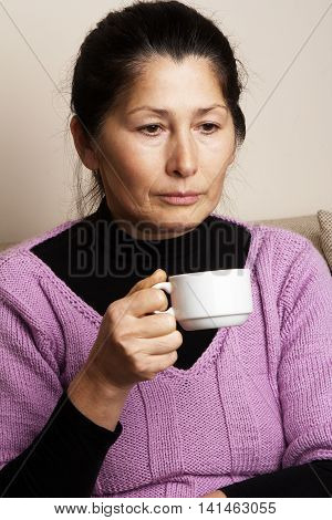 Attractive  senior woman drinking coffee at home
