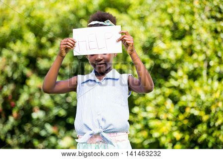 Cute mixed-race girl holding a paper with help message on a park