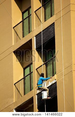 painter hanging on a rope and painting facade of high-rise building