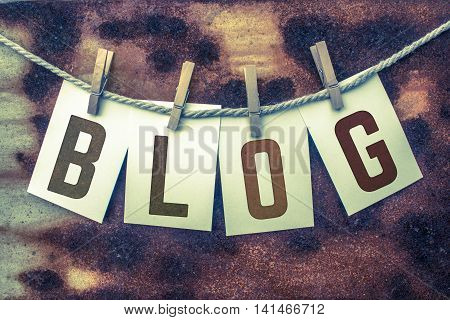 The word BLOG stamped on card stock hanging from old twine and clothes pins over a rusty vintage background.
