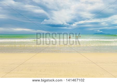 Danang, Vietnam - February 20, 2016: Tourists in the sea at the China Beach in Danang in Vietnam. It is also called Non Nuoc Beach. South China Sea and Marble Mountains on the background.
