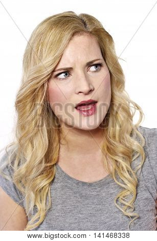 Furiously blond woman looking to the side. Angry young woman, isolated on white background.