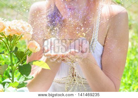 Young blonde woman blowing gold and purple glitter outdoors in summer