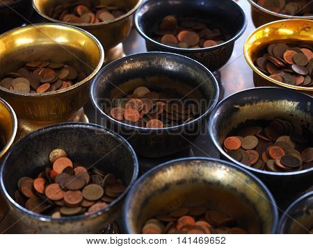 Buddhist monk's alms bowl with put coin in Thai temple
