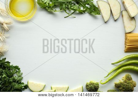 green vegetables on white background: paprika, green onion, parsley, broccoli, zucchini, aubergine, olive oil, garlic