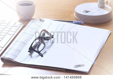 Stockbroker's desktop while taking coffee reviewing stock markets in the newspaper. Empty copy space for Editor's text.