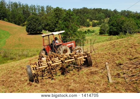 Farmer Ploughing Field On Tractor