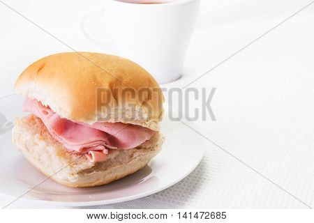 Ham bread roll or bap and a hot drink
