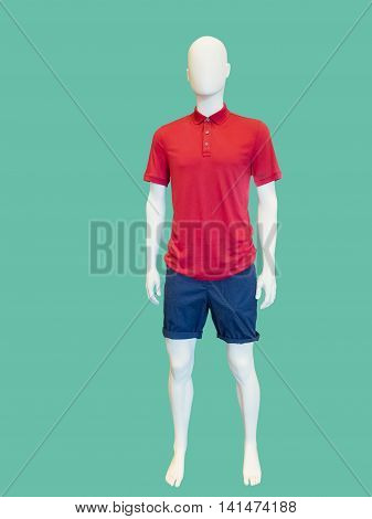 Male mannequin dressed in shorts and red t-shirt over green background.