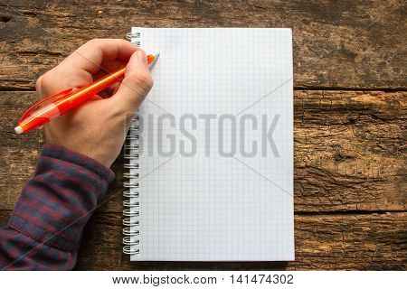left-handed man writes in a notebook on wooden background