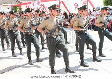Magdalena Cajamarca Peru - July 25 2016: Policemen with machine guns march in town festival in Magdalena Cajamarca Peru on July 25 2016