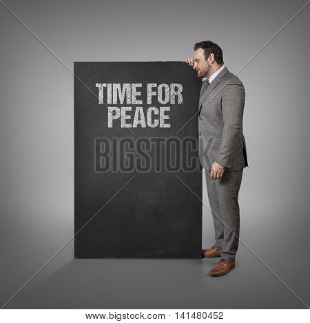 Time for Peace text on blackboard with businessman standing side