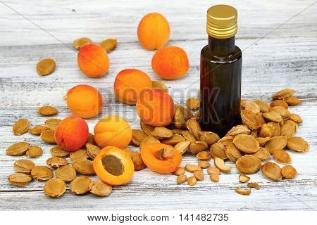 Apricot oil from apricot kernels in a brown bottle with apricot seeds around it and fresh apricots on wooden table
