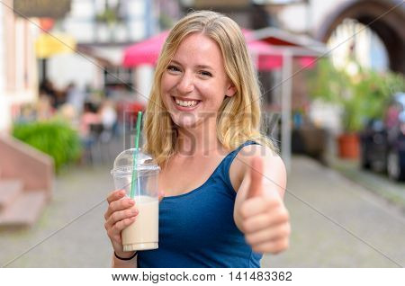 Happy Vivacious Young Woman Drinking A Takeaway