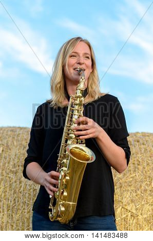 Happy Young Woman Playing A Tenor Saxophone