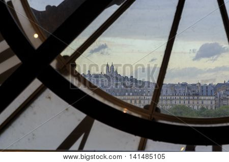 PARIS, FRANCE - MAY 14, 2015: This is view of Montmartre from window with a clock on the top floor of the Orsay Museum.