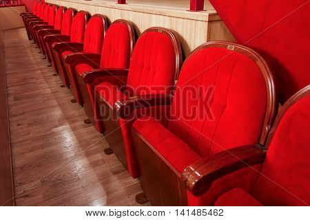 row of red velvet seats in the cinema theatre