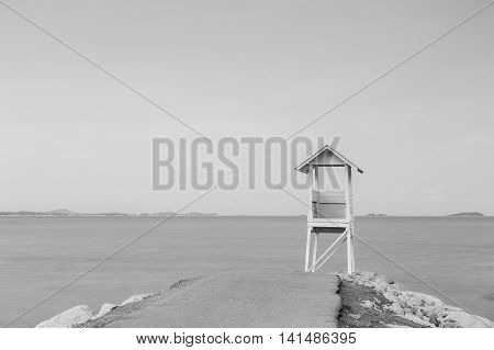 Black and White, Lifeguard station over rocky road with blue sky background
