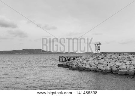 Black and White, lifeguard stand over rock on the seacoast, natural landscape background
