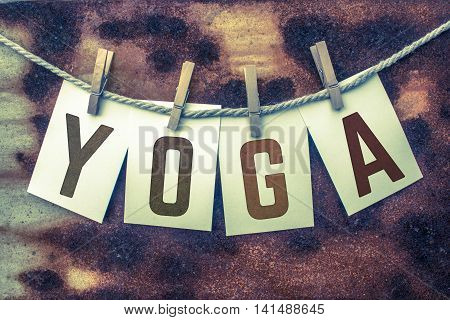 The word YOGA stamped on card stock hanging from old twine and clothes pins over a rusty vintage background.