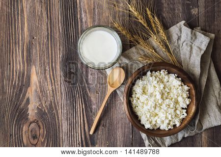Cottage cheese milk and ears of wheat on rustic wooden background. Dairy products for jewish holiday Shavuot. Top view.