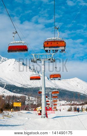 TATRANSKA LOMNICA SLOVAKIA 14 January 2015 : Chairlift on background of snowy mountains in the High Tatras at popular ski resort .