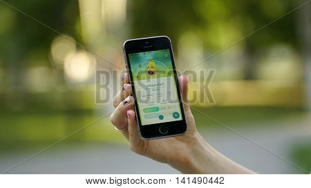 Samara, Russia - August 6, 2016: woman playing pokemon go on his iphone. pokemon go multiplayer game with elements of augmented reality. Catching the Weepinbell pokemon.