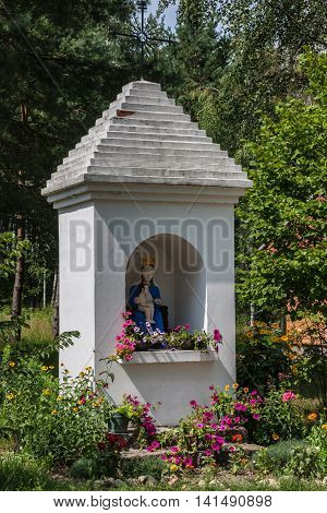 Rural roadside chapel decorated with flowers with figurines of saints
