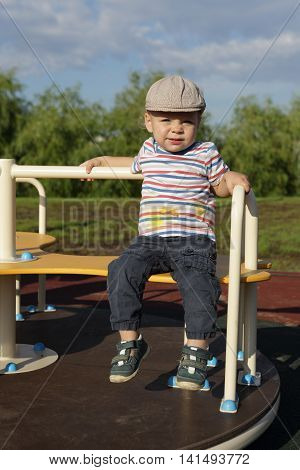 Toddler sitting on roundabout at playground in summer