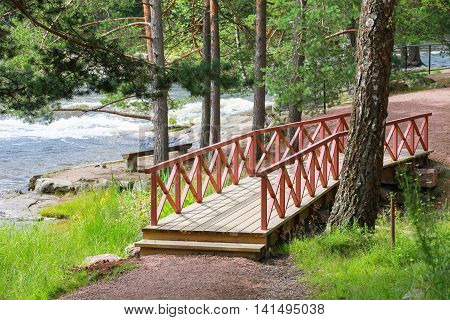 Small Wooden Bridge With Red Railings Over Stream