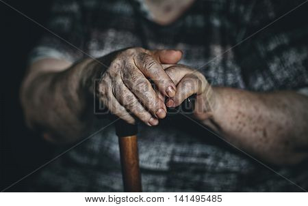 hands of an old woman senior with a cane