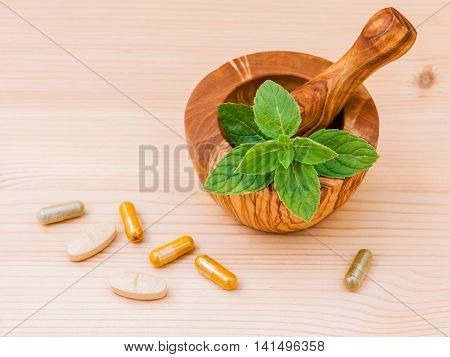 Fresh  Peppermint Leaves In Olive Wood Mortar  And Capsule Of Herbal Medicine . Alternative Health C