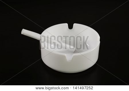 White ashtray with cigarette on the black background