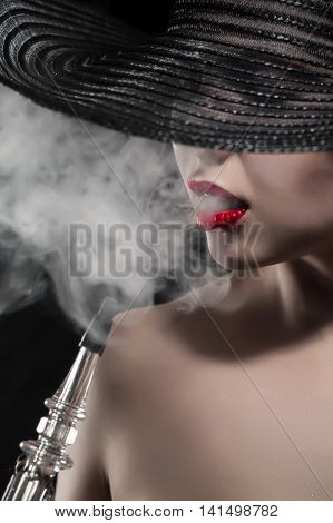 beautiful naked girl with red lips smokes hookah on black background; portrait of graceful hookah smoker woman;
