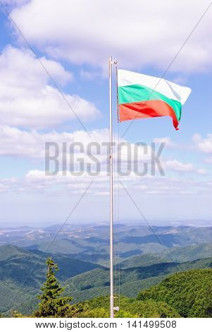 National Flag of Bulgaria with Green Mountains and Blue Sky in the Background. Location: near Shipka Memorial at Shipka Pass.