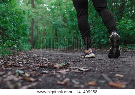 Sports shoes walking or jogging on green grass man runner cross country running on trail in summer forest. Athlete male training and doing workout outdoors in nature. Jogging workout fitness concept.